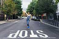 USA, New York City, Williamsburg,  woman wearing jeans dungarees posing on the street - GIOF000577