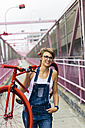 USA, New York City, Williamsburg,  woman carrying red racing cycle on her shoulder on Williamsburg Bridge - GIOF000580