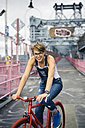 USA, New York City, Williamsburg,  portrait of blond woman with red racing cycle on Williamsburg Bridge - GIOF000583