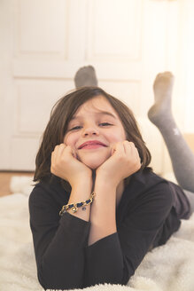 Portrait of smiling girl with head in hands lying on blanket on the floor - LVF004228