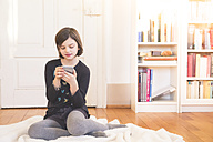 Portrait of girl sitting on blanket on the floor using smartphone - LVF004234