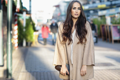 Portrait of young woman with long brown hair wearing light brown coat - GDF000936