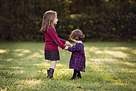 Two little girls dancing hand in hand on a meadow - LITF000072
