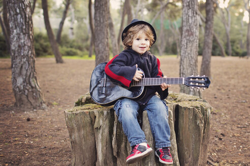 Portrait of little boy playing guitar in a forest - LITF000082