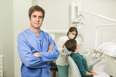 Portrait of confident dentist with assistant and patient in background - JASF000301