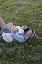 Happy couple in love lying on a meadow - BOYF000011