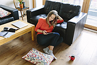 Young woman sitting on the floor of her living room looking at digital tablet - BOYF000019