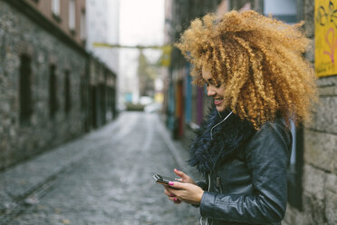 Ireland, Dublin, smiling woman with afro looking at her smartphone - BOYF000033