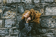 Woman with afro hearing music with earphones in front of a natural stone wall - BOYF000036