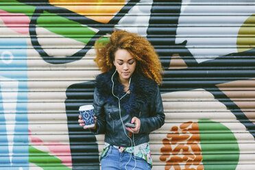 Woman with afro hearing music with smartphone and earphones - BOYF000039