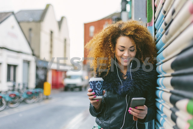 Ireland, Dublin, smiling woman with coffee to go hearing music with smartphone and earphones - BOYF000042 - Boy/Westend61