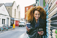 Ireland, Dublin, smiling woman with coffee to go hearing music with smartphone and earphones - BOYF000042