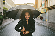 Portrait of smiling woman with umbrella on a rainy day - BOYF000045