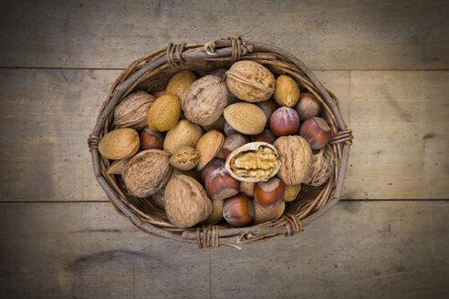 Wickerbasket of walnuts, almonds and hazelnuts on wood - LVF004261
