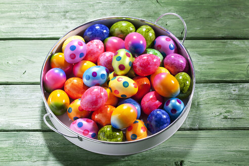 Tray of coloured Easter eggs on green wood - CSF026918