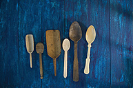 Different wooden spoons and shovels on blue wood - ASF005779