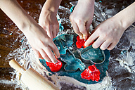 Hands of two children cutting out Christmas cookies - SARF002385
