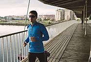 Spain, Naron, jogger running on a wooden bridge - RAEF000697