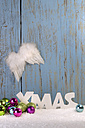Christmas decoration with baubles, angel wings and artificial snow in front of wooden wall - LBF001306