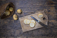 Wickerbasket, whole and sliced swedes, wooden board and a knife on dark wood - LVF004269