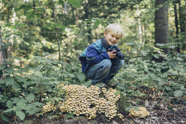 Germany, Saxony, smiling boy with camera n the woods - MJF001687