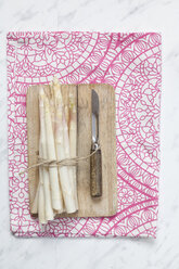 Bunch of white asparagus, chopping board and peeler - SBDF002569