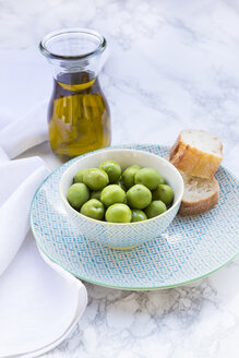 Bowl of green olives, slices of bread and carafe with olive oil - LVF004294
