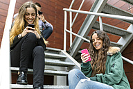 Three friends hanging around with cell phones oudoors - MGOF001143