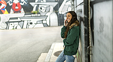 Smiling young woman on cell phone leaning against a wall - MGO001146