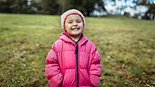 Portrait of smiling little girl wearing cap and pink jacket in autumn - MGOF001156
