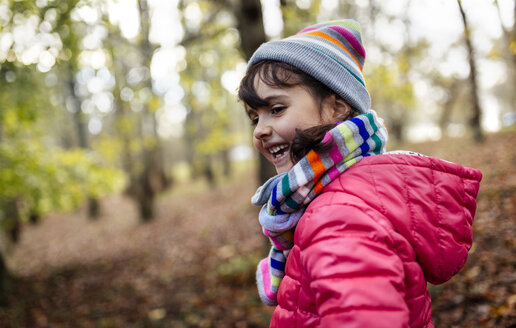 Happy little girl in the woods wearing cap and scarf in autumn - MGOF001159