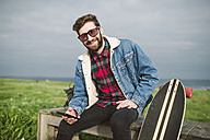 Young casual man sitting in a park with his longboard, he is smiling and looking at camera - RAEF000712
