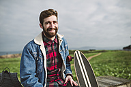 Young casual man, smiling, with longboard - RAEF000715