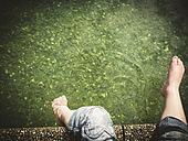 Girl's feet at the edge of a lake - GSF001044
