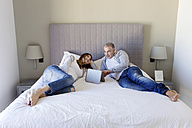 Couple with digital tablet relaxing on bed - LITF000121