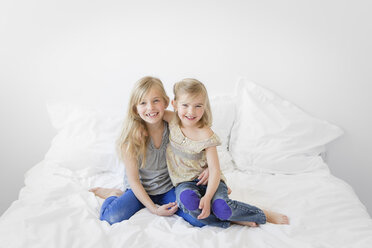Portrait of two little sisters sitting on a bed - LITF000129