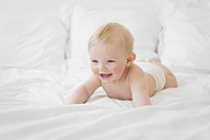 Portrait of smiling blond baby boy only wearing diaper lying on a bed - LITF000132