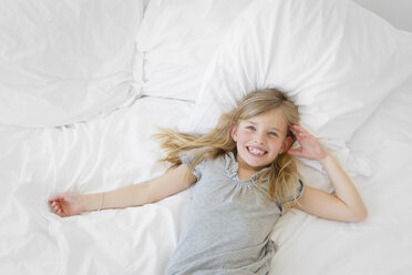 Blond little girl with toothgap lying on a bed looking at camera - LITF000138