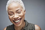 Portrait of laughing woman with eyes closed in front of grey background - RHF001083