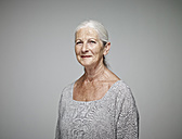 Portrait of smiling senior woman in front of grey background - RHF001107