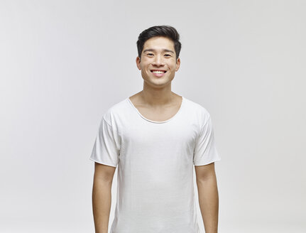 Portrait of smiling young man wearing white t-shirt - RHF001128