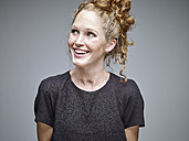 Portrait of smiling young woman with curly blond hair in front of grey background - RHF001137