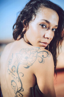 Portrait of woman with tatoo on her back looking over her shoulder - EHF000333