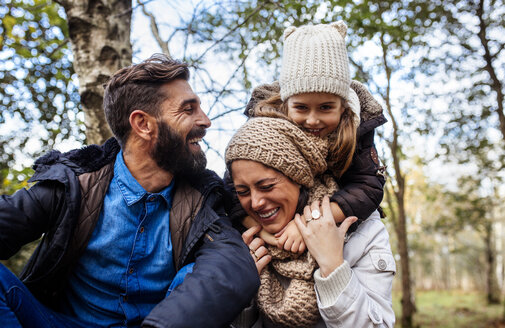 Happy parents with daughter in the forest - MGOF001169