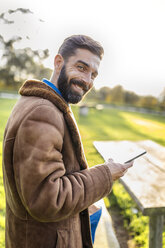 Portrait of smiling man with cell phone outdoors - MGOF001178