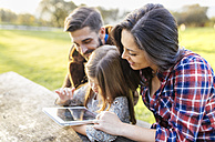 Happy parents with daughter using digital tablet outdoors - MGOF001181