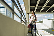 Young woman with earbuds and cell phone in parking garage - UUF006164