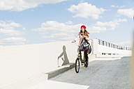 Young woman riding bicycle holding cell phone - UUF006176