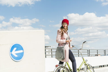 Young woman on bicycle holding cell phone - UUF006182