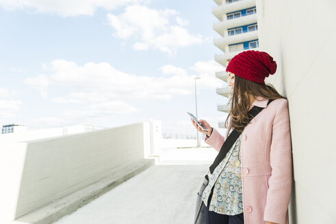 Young woman leaning against concrete wall looking at cell phone - UUF006185